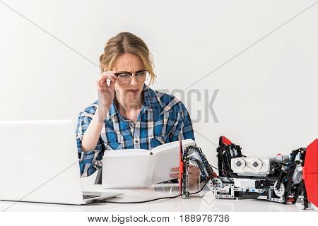 Cannot understand. Portrait of concentrated young woman is reading instructions to robot and expressing incomprehension. Isolated background
