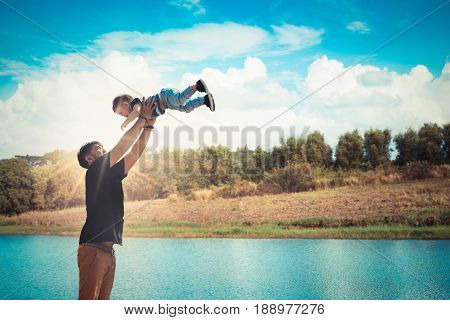 Father throwing his son at the river park. Concept of friendly family.