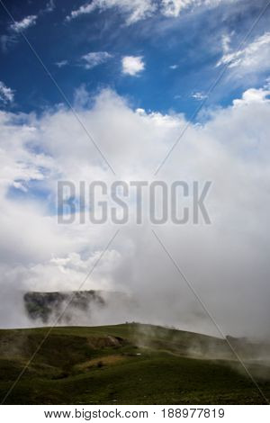 The dense fog, green slopes tightened by white clouds, a picturesque landscape