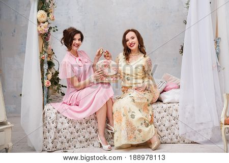 Happy girlfriends smile and show each other jewelry, sitting in their bedroom.