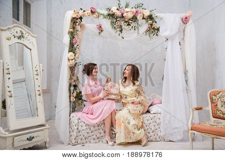 Happy girlfriends smile and show each other jewelry, sitting in their bedroom
