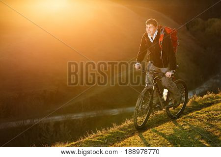 Cyclist stands up to pedal along a steep climb. Cyclist pedaling uphill with a backdrop at sunset. Green field and grass. Beautiful landscape. Cyclist with red backpack. Spring season. Travel in the countryside.