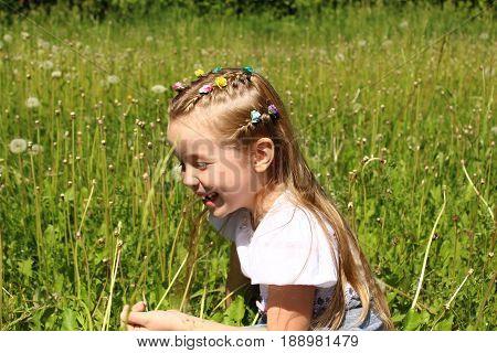 Girl in a field of ripened dandelion