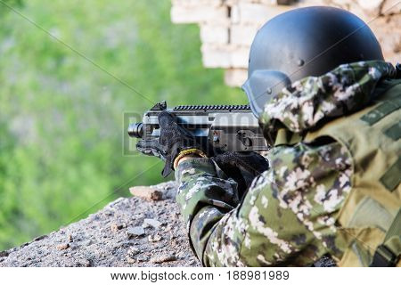 The Soldier Aims From The Combat Position. Military Actions Among The Destroyed Buildings. Assault A