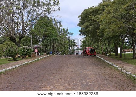 Strassenscene gepflasterte Strasse mit rotem VW Kaefer Aregua Paraguay