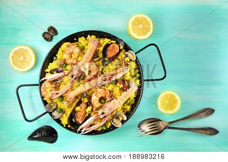 Photo of Spanish seafood paella in typical paellera, with slices of lemons, mussels and clams shells, fork and spoon, and a place for text, shot from above on a teal texture