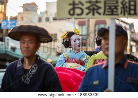 KYOTO, JAPAN - NOVEMBER 11, 2016: Maiko women, apprentice geisha on the street parade in Kyoto, Japan. Kyoto was formerly the Imperial capital of Japan for more than one thousand years.