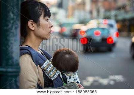 KYOTO, JAPAN - NOVEMBER 11, 2016: Unidentified japanese woman with a baby sling on the pedestrian crossing of Kyoto, Japan. Kyoto Metropolis is one of the most populous city of Japan.