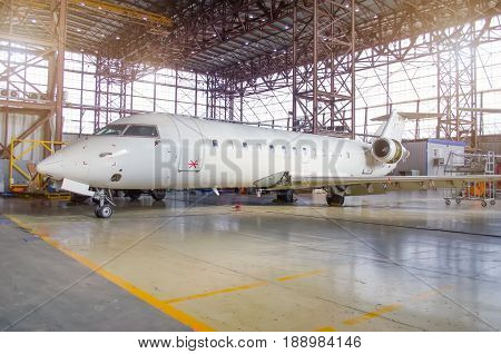 White aircraft in the hangar on a large-scale inspection, repair
