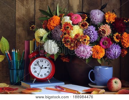 Bouquet of autumn flowers a stack of books autumn leaves and red alarm clock on the table. Back to school. The teacher's day. The first of September.