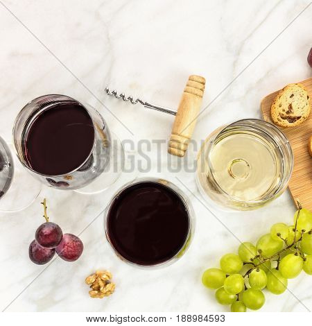 A square photo of glasses of red and white wine at a tasting, with grapes and a place for text