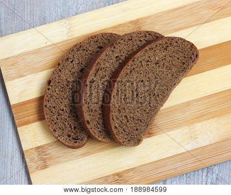 Rye bread cut into pieces lies on a chopping Board top view. Three pieces of rye bread.