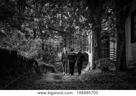 Three young people walking through an abandoned camp mysterious and mysterious atmosphere in a black and white photo