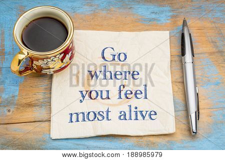 Go where you feel most alive - inspirational handwriting on a napkin with a cup of coffee