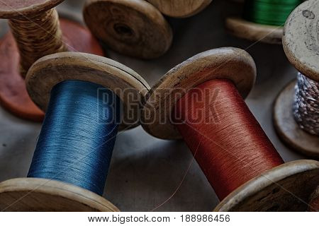 Vintage wooden spools with silk threads in a variety of colors including blue red green and gold.