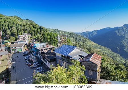 View from top of Kaluk a small town at Sikkim India - surrounded by Himalayan mountains . A blue clear sky above.