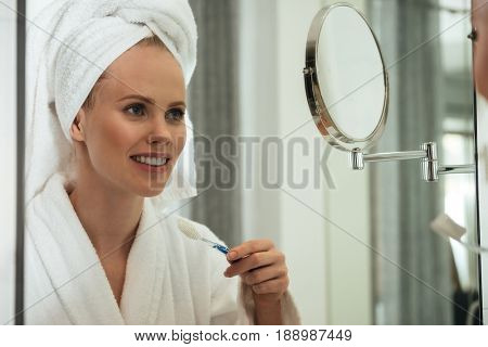 Young blonde woman with towel on head and wearing bathrobe brushing teeth against mirror in bathroom