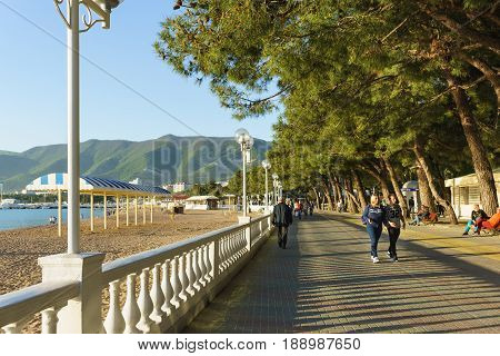 Gelendzhik Krasnodar Krai Russia - April 29.2017: People walk along the embankment of Gelendzhik on the background of mountains and alleys of pine trees in sunset