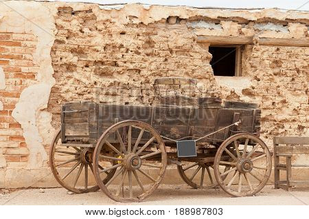 Vintage heritage horse cart standing in front of weathered mud brick wall history scene near Tucson Arizona AZ USA