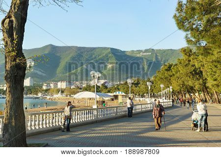 Gelendzhik Krasnodar Krai Russia - April 29.2017: People walk along the embankment of Gelendzhik on the background of mountains in the rays of the setting sun