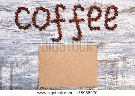 Coffee beans and piece of paper. Coffee decoration on wooden background. Coffee makes closer.
