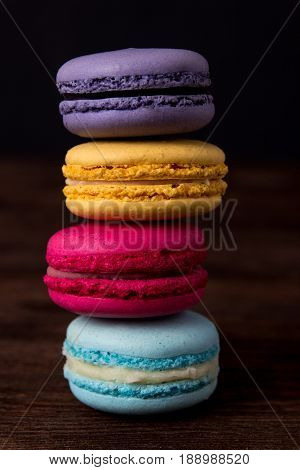 Colorful macaroons on dark wooden background. Macaroons close up