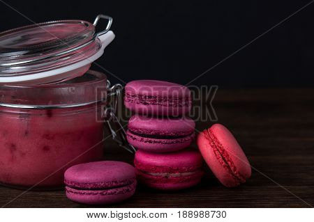 Pink macaroons with raspberry jam on dark wooden background. Berry macaroons on dark background