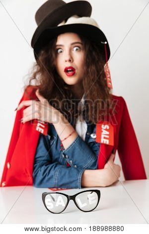 Image of shocked young lady dressed in a lot of clothes and hats by sale sitting at the table isolated over white background. Looking at camera. Focus on glasses on table.