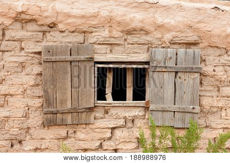 Window opening with old wooden shutters in weathered mud brick wall near Tucson Arizona AZ USA