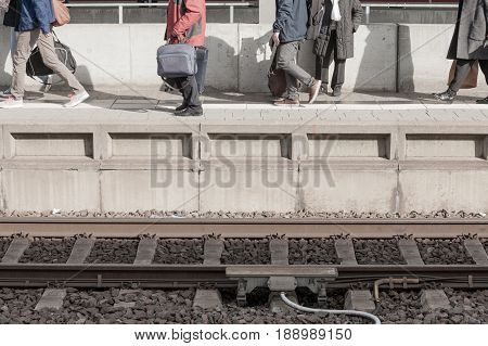 Travelers moving on railway station platform to catch train to arrive on railroad tracks at bottom of concrete platform