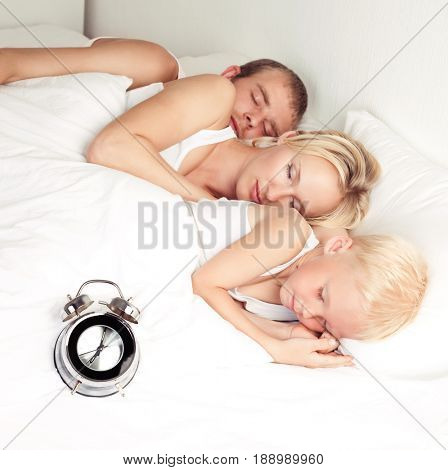 happy family: father, mother and son sleeping in bed at home