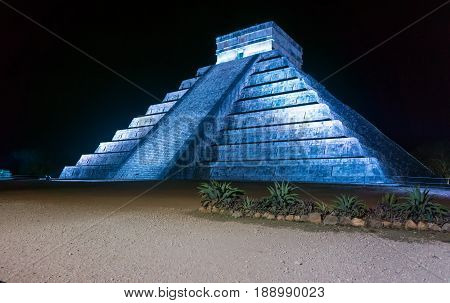 Kukulcan pyramid in blue light at night in Chichen Itza in Mexico