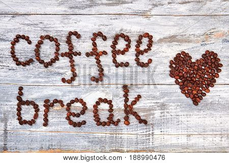 Coffee break and coffee heart. Heart from grain on table. Lovely coffee pause.