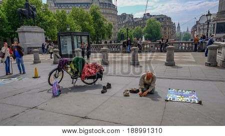London UK - May 11 2017: Old man street artist kneeling in Trafalgar Square counting coins in a heart shape with bike and shoes beside him.