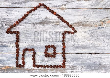 House from coffee beans. Building from coffee, wooden background. Drink coffee and feel coziness.