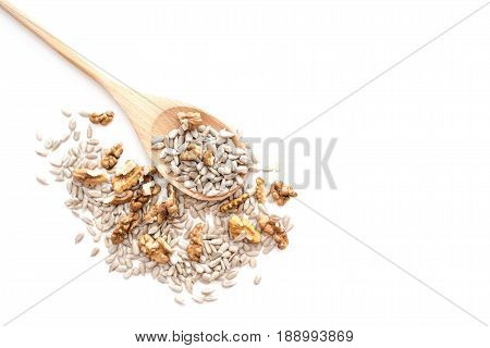 Dried peeled sunflower seeds with walnuts on wooden spoon isolated on white background