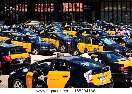 BARCELONA, SPAIN - APRIL 17: Travelers and numerous taxis waiting in front of the railway station Barcelona-Sants on April 17, 2013 in Barcelona, Spain