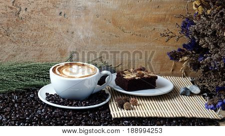Hot cappuccino or latte art coffee and chocolate brownies cake. A cup of coffee on the wooden table with dark roasted coffee beans. Morning breakfast with coffee. Flower shape created by milk.