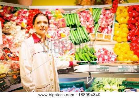 sales clerk at the supermarket with fresh veggies