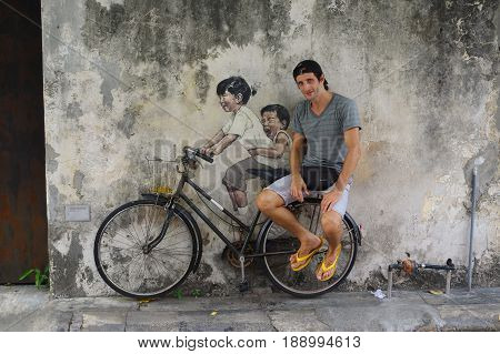 PENANG, MALAYSIA - APRIL 18, 2016: a Local tourist poses in-front of Street Mural tittle 'Little Children on a Bicycle' painted by Ernest Zacharevic in Penang on July 6, 2013 in George Town