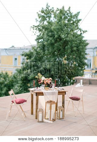 Wedding decor. Perfectly decorated holiday table for two with beautiful flower composition on rooftop on green tree background, glasses for wine, big candles. romantic dinner concept. fine art.
