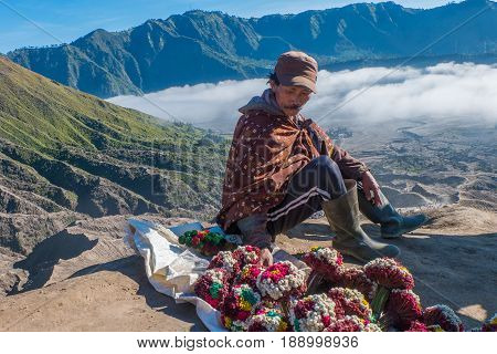 Mount Bromo,Java,Indonesia-May 10,2017:Local man selling dried flowers at the Bromo crater rim in Mount Bromo,Java,Indonesia.Mount Bromo,a popular tourist attraction on Indonesia's island of Java,