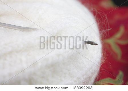 Crochet Angora Yarn Head Cap and Crochet Hook on a Red Background