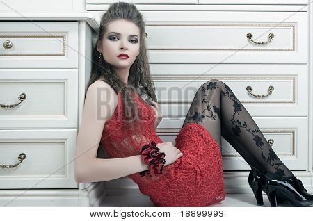 sexy fashion model sitting on floor in red dress