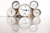 Row of metal steel high pressure gauge meters or manometers with brass fittings on tubing pipeline at LNG or LPG natural gas distribution station plant or factory facility isolated on white background.Pressure gauge in oil and gas production process. poster