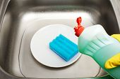 Close up kitchen sink with water clean white plate blue cleaning sponge and bottle of liquid detergent in female hand in yellow protective rubber glove poster