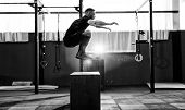 Fit young man jumping onto a box as part of exercise routine. Man doing box jump in the gym. Athlete is performing box jumps poster
