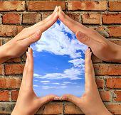 Home symbol made from hands over a brick with a window into blue sky conceptual photo illustration poster