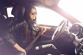 Brunette in sunglasses woman fastens with a belt in an expensive car. Safety first. Beautiful caucasian lady fastening car seat belt. poster