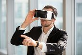 Businessman using technology of augmented reality in daily office work. Man ceo wearing virtual reality glasses, pointing at the air. Office worker in electronics 3d goggles interacts with simulation poster